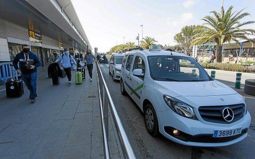 Varios taxis esperan viajeros en el aeropuerto.