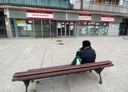 Una mujer, sentada frente a una oficina de empleo.