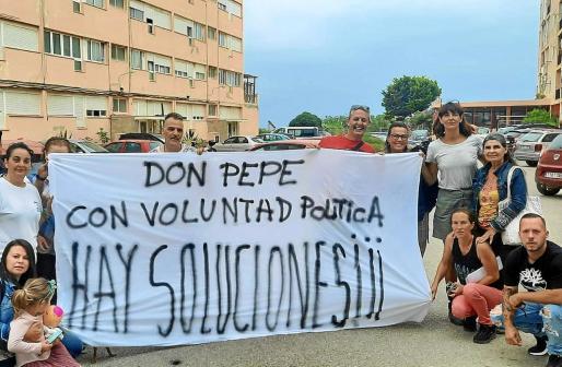 Los afectados por el desalojo posan junto al edificio con una pancarta.