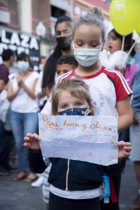 """Dos niñaas con un cartel, en homenaje a Anna y Olivia, participan en una concentración feminista en la Plaza de la Candelaria en repulsa por """"todos los feminicidios"""", a 11 de junio de 2021, en Santa Cruz de Tenerife."""