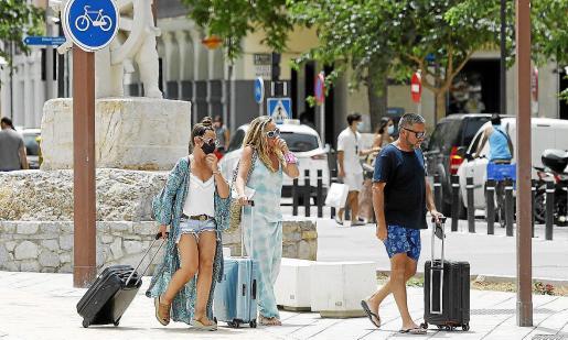 Un grupo de turistas camina por Vila con sus maletas.