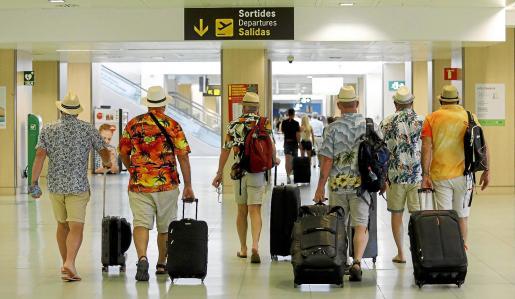 Un grupo ed turistas británicos se dirige a la terminal tras disfrutar de sus vacaciones en Ibiza.