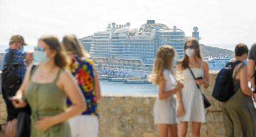 Uno de los grupos de cruceristas que pasearon ayer por Dalt Vila con el 'Aida Perla' al fondo.