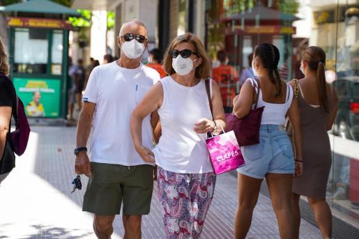 Gente caminando por las calles de Ibiza con mascarilla.