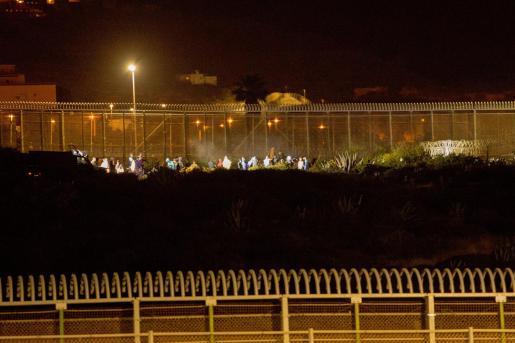 Varios marroquíes intentan llegar a suelo español desde la frontera que separa Melilla y Marruecos en una imagen de archivo.