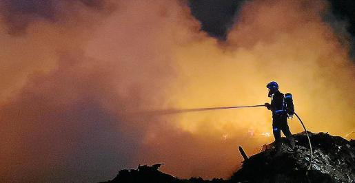 Un bombero durante el retén nocturno en la montaña de plásticos de Ca na Putxa.