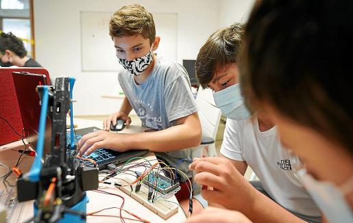 Toni, Victor y Marc trabajan en la parte electrónica de su brazo robótico.