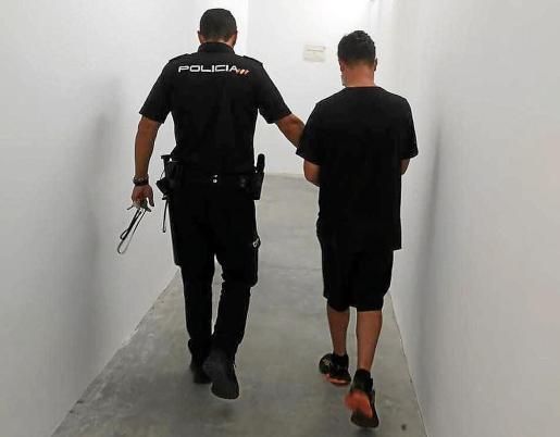 Un agente de la Policía Nacional custodia al investigado en su puesta a disposición judicial.