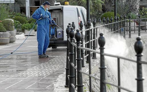 Un operario limpiando el paseo marítimo de Santa Eulària.