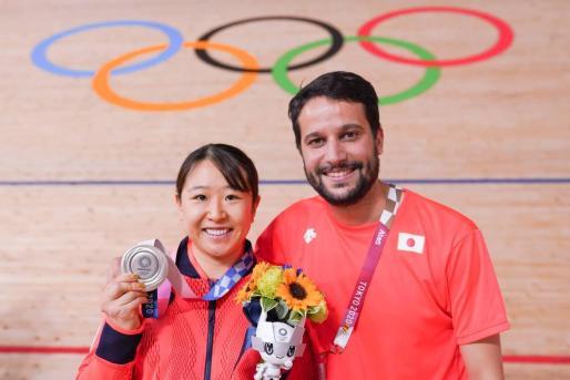 Yumi Kajihara muestra su medalla de plata en Omnium junto al técnico ibicenco Miguel Torres.