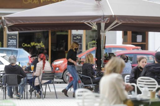 Sílvia Moreta sirve un desayuno en la terraza de su negocio en la plaza de Sa Graduada.