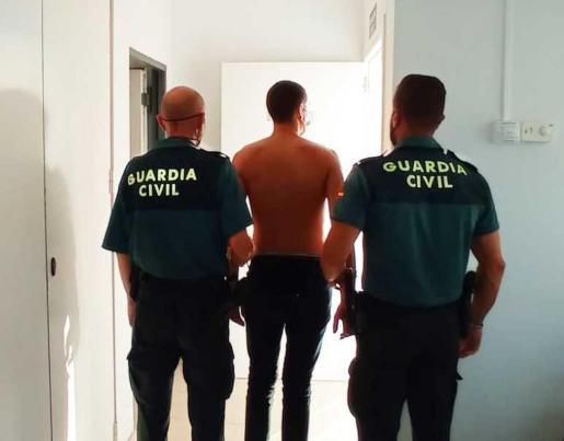 Dos guardias civiles custodian al joven colombiano detenido por tráfico de drogas.