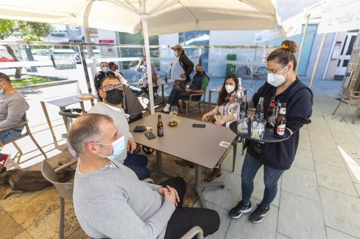 Una camarera sirve en una terraza a unos clientes.