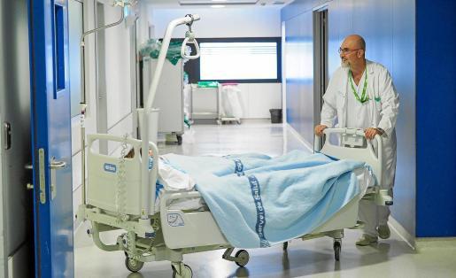 El celador Joan Marí Baeza trasladando a un paciente ingresado.