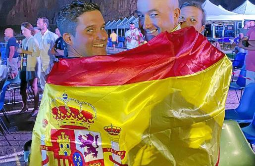 Óscar Cervantes, a la izquierda, posa con la bandera de España junto a un amigo.