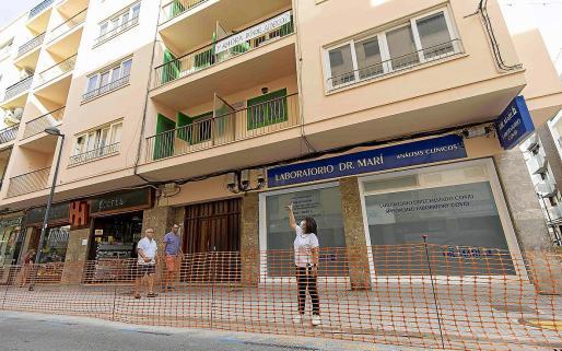 Los vecinos y comerciantes de la Calle Aragón ya muestran su descontento con la ampliación de aceras en detrimento de plazas de aparcamiento. La presidenta de los comerciantes, Encarna Planells, señala una pancarta en un balcón.