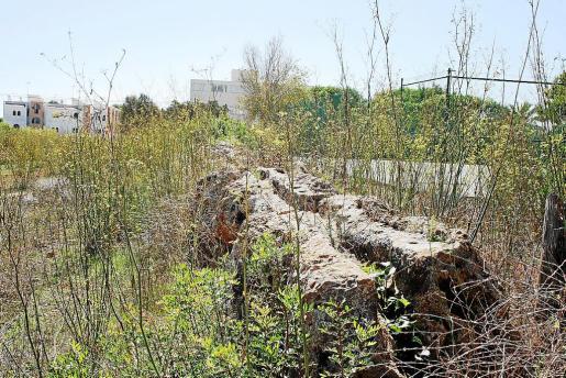 El acueducto, en primer término. Al fondo, en el centro de la imagen, el edificio que será demolido.