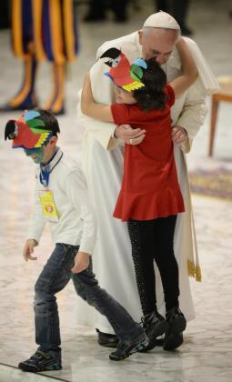 El papa Francisco abraza a un niño durante una audiencia.