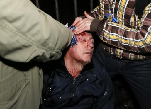 El ex ministro del Interior de Ucrania y líder de la oposición Yuriy Lutsenko recibe asistencia médica tras los enfrentamientos.