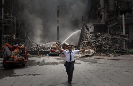 Un guarda de seguridad aleja a los curiosos de la zona comercial del centro de la ciudad, tras una noche de incendios y saqueos. g Foto: ADREES LATIF/REUTERS