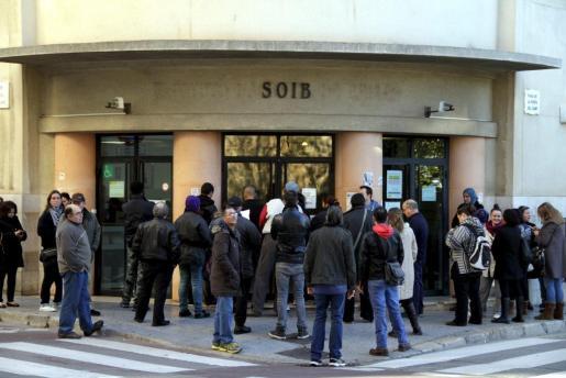 Algunas personas esperan frente a la oficina del paro en Palma a su apertura.