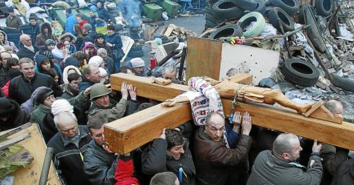 Un grupo de personas traslada un crucifijo durante un servicio religioso en el lugar de los enfrentamientos en Kiev.