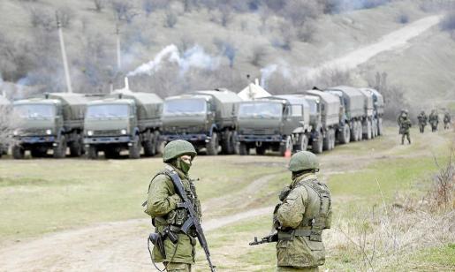 Hombres armados, posiblemente soldados rusos, están de guardia fuera de una unidad militar de Ucrania, cerca de Simferopol.