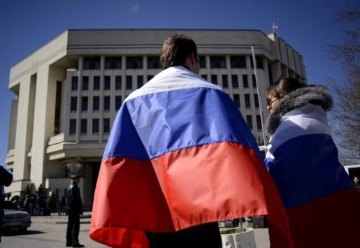 Un hombre y una mujer lucen banderas rusas sobre sus hombros frente al Parlamento de Crimea.