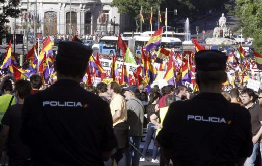Dos policías ante los manifestantes que se han congregado en la Plaza de Cibeles, en Madrid, en favor de un referéndum sobre monarquía o república.