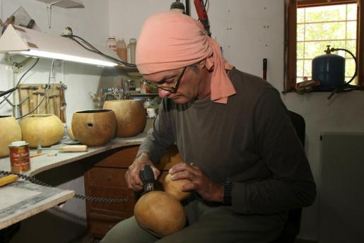 El artesano italiano muy concentrado en su taller de trabajo mientras empieza a cortar una calabaza que más tarde se convertirá en jarrón o frutero.