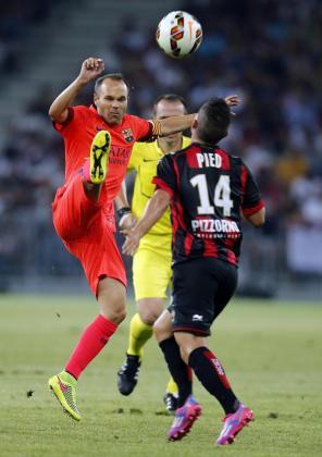 El jugador del Barcelona Andrés Iniesta lucha un balón con el jugador del Niza Jeremy Pied.