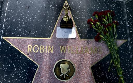 Un ramo de flores y una estatuilla del premio Oscar decoran la estrella del actor estadounidense Robin Williams en el Paseo de la Fama hoy, lunes 11 de agosto de 2014, en Hollywood, Los Ángeles (CA, EE.UU.). El famoso actor de Hollywood Robin Williams fue hallado muerto hoy en su domicilio en el norte de California (EE.UU.).