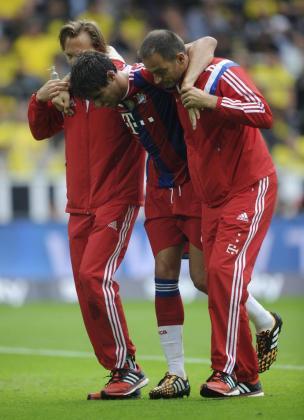 El centrocampista español del Bayern de Múnich Javi Martínez (c) se retira del campo ayudado por dos miembros del personal médico durante el partido de Supercopa entre el Borussia y el Bayern de Múnich en el estadio Signal Iduna en Dortmund.