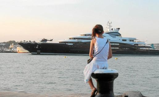 Una turista observa el Serene, yate de Bill Gates, atracado en el puerto de Eivissa este verano. Su alquiler cuesta 350.000 euros a la semana.