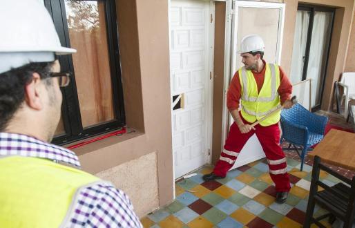 Uno de los empleados desmontando una de las puertas de la vivienda.