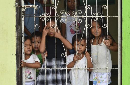 Varios niños miran tras la verja de un colegio reconvertido en centro de evacuación en la localidad de Ormoc, en la provincia de Leyte (Filipinas), el pasado viernes 5 de diciembre de 2014. Este pueblo fue fuertemente dañado por el paso del tifón Haiyan hace un año.