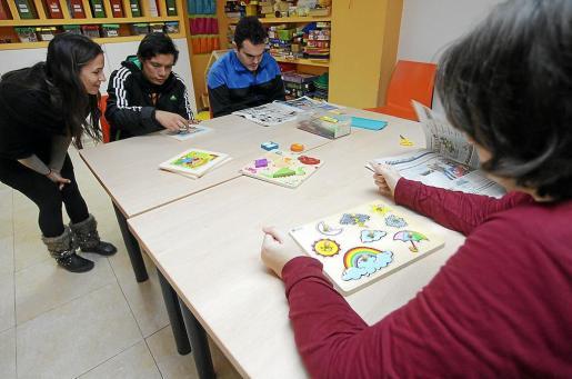 Varios pacientes realizando actividades y leyendo varios ejemplares de Periódico de Ibiza ante la mirada de una de las coordinadoras.