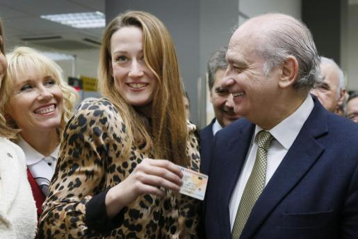 El ministro del Interior, Jorge Fernández Díaz (d), posa junto la nadadora olímpica Mireia Belmonte (2i), a quién se ha expedido el primer DNI electrónico 3.0, durante la presentación de este lunes en Lleida de este nuevo carné que permite la transmisión de datos vía NFC.