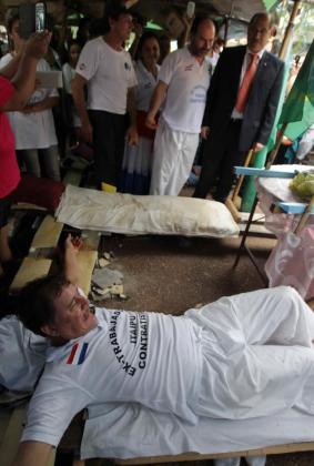 El ministro paraguayo de Trabajo, Guillermo Sosa (d), observa al manifestante Guillermo Sosa (abajo), este jueves 29 de enero de 2015, durante el levantamiento de la protesta de cinco trabajadores que se crucificaron afuera de la embajada brasileña, en Asunción (Paraguay).