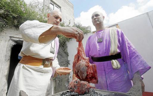 Dos actores interpretando a sacerdotes mientras realizan un sacrificio animal para honrar a la diosa Tanit y pedir la salvación de un gerrero. Foto: DANI ESPINOSA