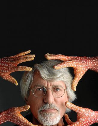 Guido Daniele junto a cuatro manos pintadas por él mismo.