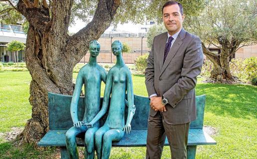 El director de Ibiza Gran Hotel, Raúl Sierra, posa en el jardín del establecimiento con una de las obras de arte.