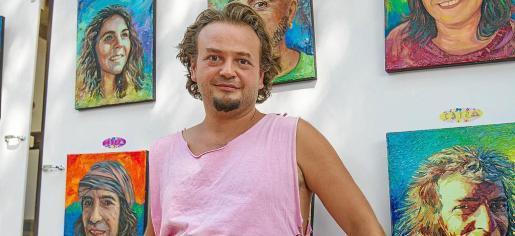 El artista búlgaro posa con algunos de los 18 retratos que forman parte de la exposición 'Iconos de Ibiza'.