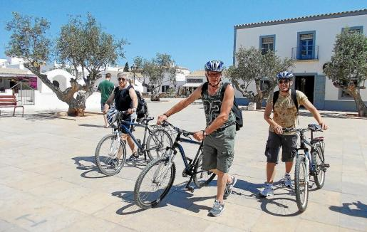 Tres amigos se disponen a aparcar sus bicis en la plaza de Sant Francesc de Formentera.