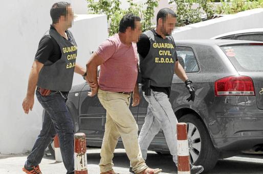 Dos agentes de la Guardia Civil custodian uno de los detenidos en el edificio El Faro II de Sant Antoni de Portmany.