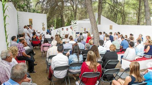 Los fieles siguieron la misa entre los muros de la iglesia descubierta y cobijados bajo los pinos.