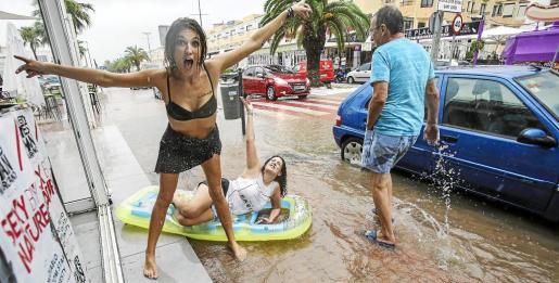 Una pareja de turistas británicas se divierte con una colchoneta en la calle, completamente anegada, ante la mirada sorprendida de un viandante que camina bajo la lluvia. Foto: ARGUIÑE ESCANDÓN