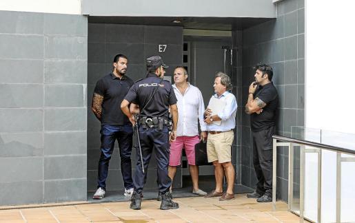 El arrendatario Juan Carlos Pereira y su abogado conversan con los agentes a la entrada del edificio.