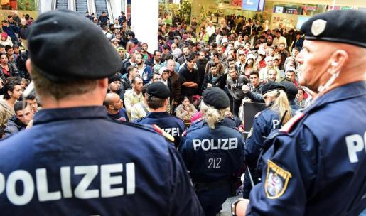Policías forman un cordón frente a los cientos de refugiados que esperan la llegada de más trenes con dirección a Alemania en la estación de Salzburgo (Austria).