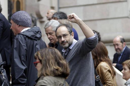 El lider de la CUP, Antonio Baños, saluda a los ciudadanos congregados a las puertas del Tribunal Superior de Justicia de Catalunya (TSJC), desde la comitiva que ha acompañado a la consellera de Educación de la Generalitat, Irene Rigau, a declarar ante el TSJC para aclarar su papel en la organización de la consulta alternativa independentista del 9N.